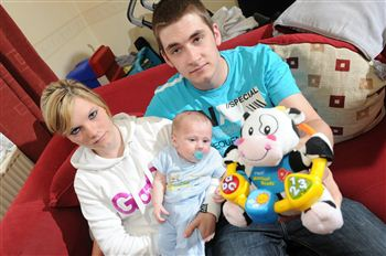 Jodie Cairns and Zac Walker with baby Ethan and the offending cow