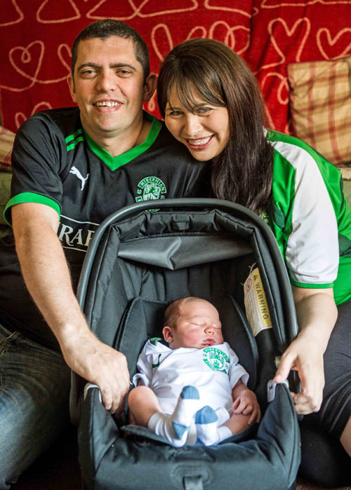 Stuart and Fiona with baby Stuart, showing off their team colours.