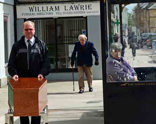 William Lawrie tries to avoid elderly pedestrians while wheeling coffins in the street.