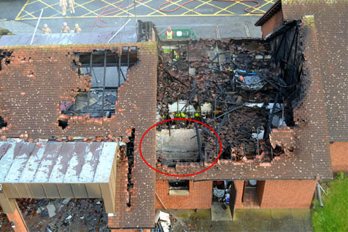 The fire started in a workshop, circled here in this official report photograph