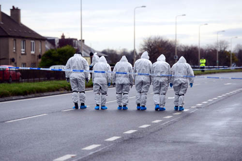 A police forensic squad check the road - that would normally be packed with traffic - for clues