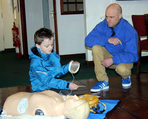 Alan's son Sam, 8, demonstrates how to use the defibrillator.