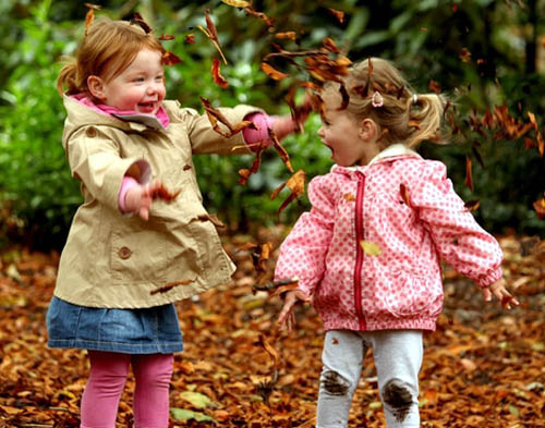 Children enjoy the simple pleasure of playing with autumn leaves at the Royal Botanic Garden, Edinburgh
