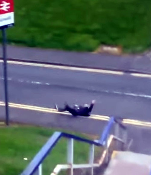 He ends up lying down in the road with his legs in the air