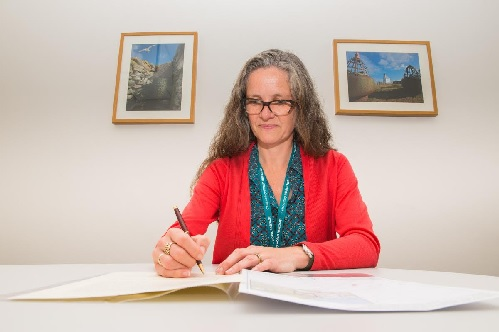 Barbara Cummins signs the document