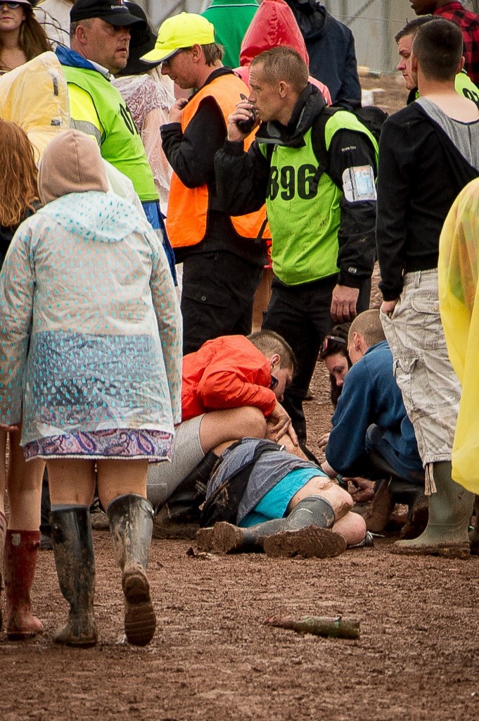 T in The Park, 2015, Day two. T in The Park has it's first day on it's new site at Strathallan Castle. Thousands of festival goers brave the rain to attend the 22nd TiTP. IN PIC................. Security attempt to revive a reveler between the campsites and the arena. (c) Wullie Marr/DEADLINE NEWS For pic details, contact Wullie Marr........... 07989359845
