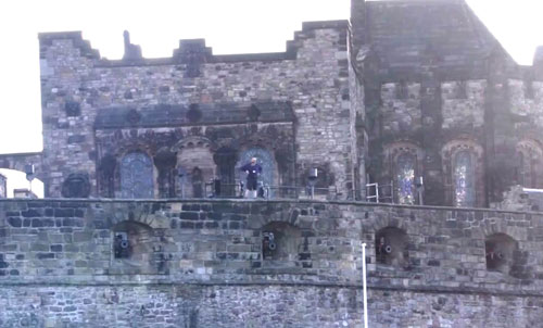 The man appears to be dancing on the castle walls