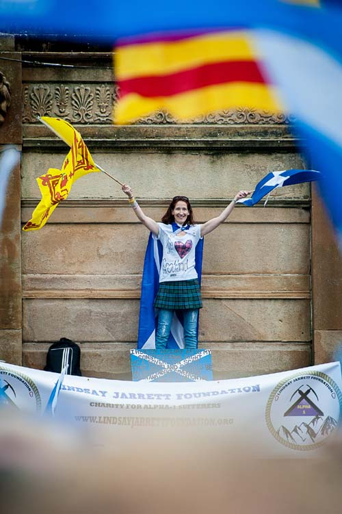 A pro-independence supporter waves her flags from a monument