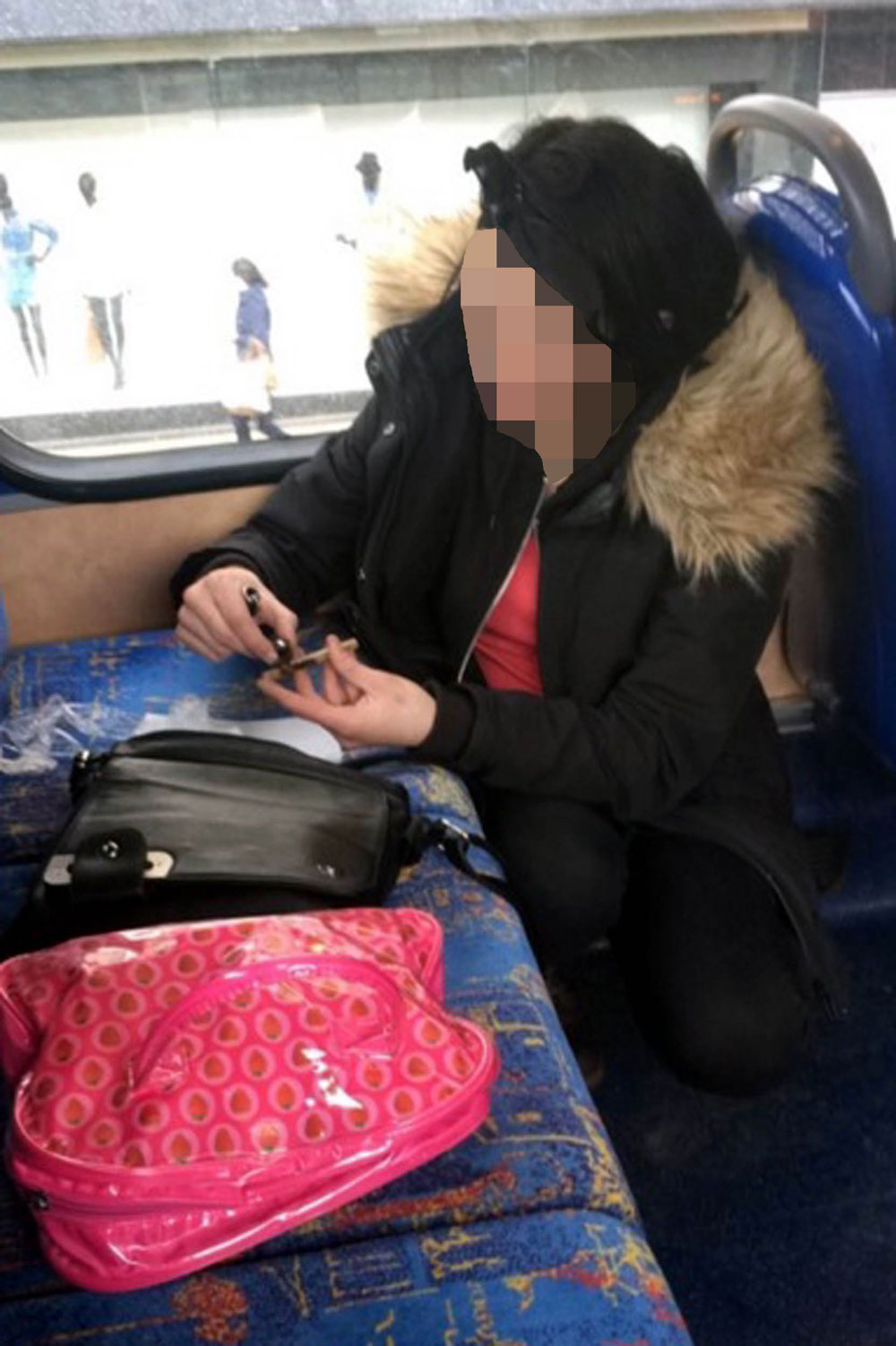 The woman prepares a pipe at the back of the bus
