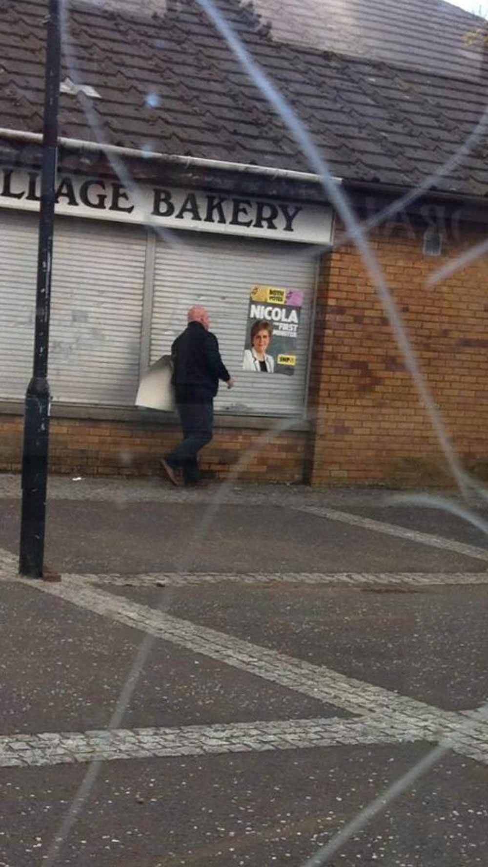 The second image appears to show him removing a poster from a shopfront