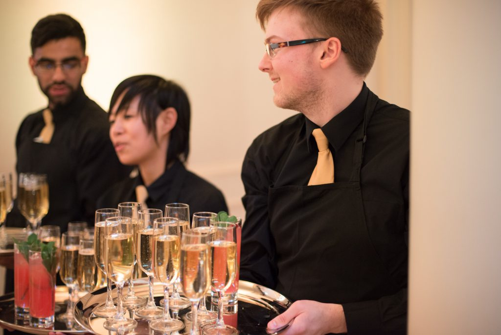 People with tray of drinks at an event