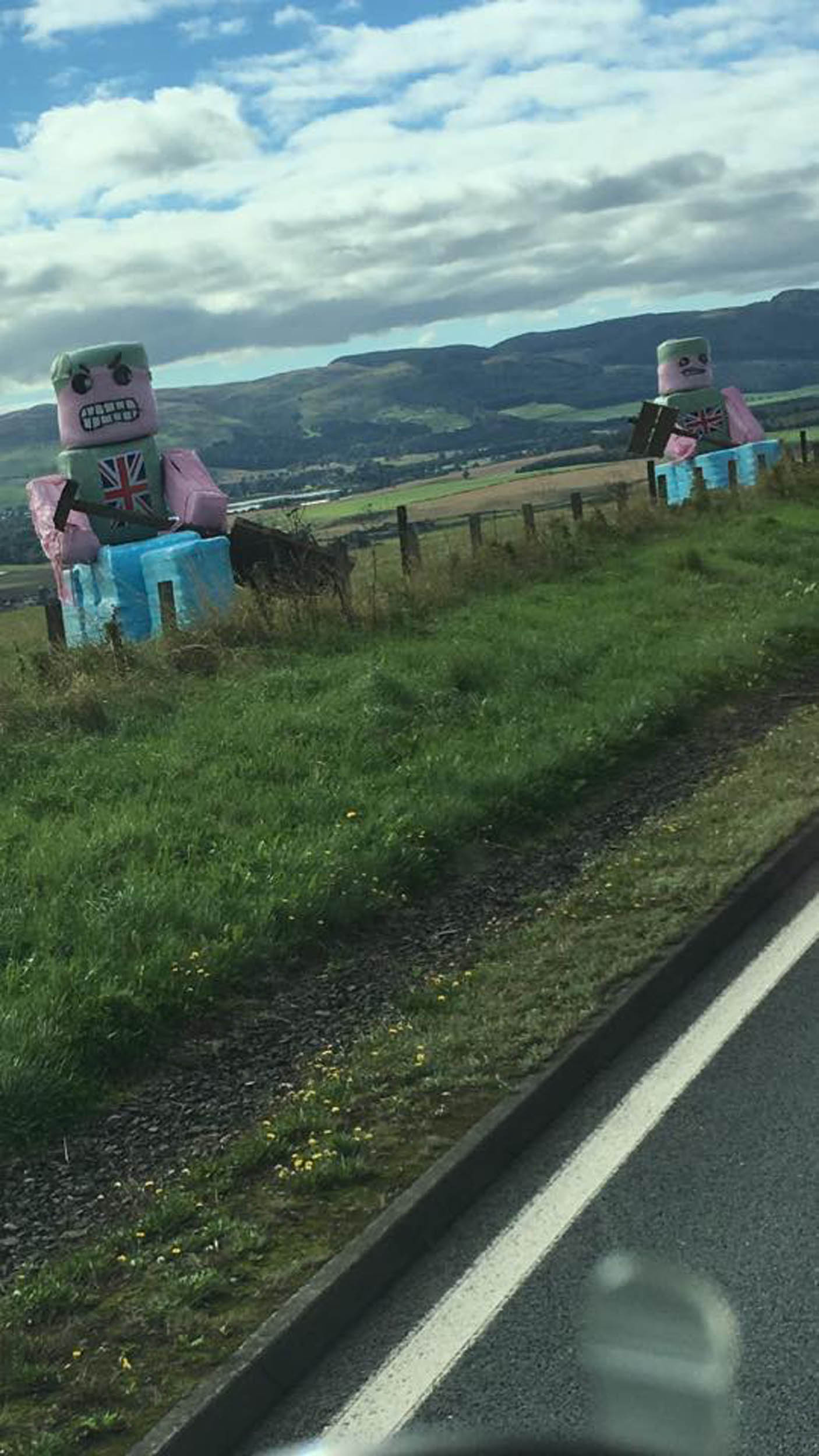 The statues are next to the A9, one of Scotland's busiest roads A PROUD dad has immortalised his sports star sons by creating two 15ft-high statues - made from hay bales. Billy Fotheringham made the giant canoes and canoeists after his boys were selected to represent the UK. The 45-year-old used different blue, pink and grey plastic on the hay bales to create the canoes before adding wooden paddles and Union Jacks. The statues were created right next to one of Scotland's busiest roads - the A9 as it passes Bankhead Farm, near Perth. Sandy, 18, and Wills, 16, were selected to represent GB in wild water canoe racing, taking part in the under-23 category at international championships in Austria this July. Billy said the statues are intended to help raise money for the boys, who spend more than £1,000 each getting their canoes to international events.