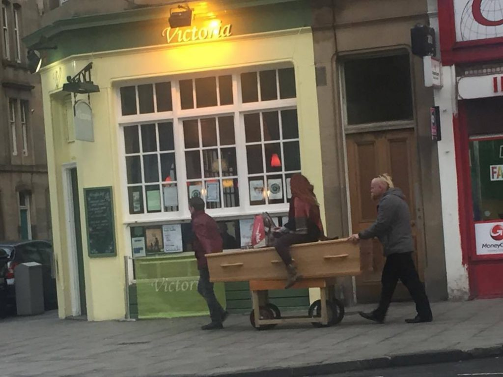A BIZARRE image of a woman riding a coffin down a city centre street has surfaced on social media.
