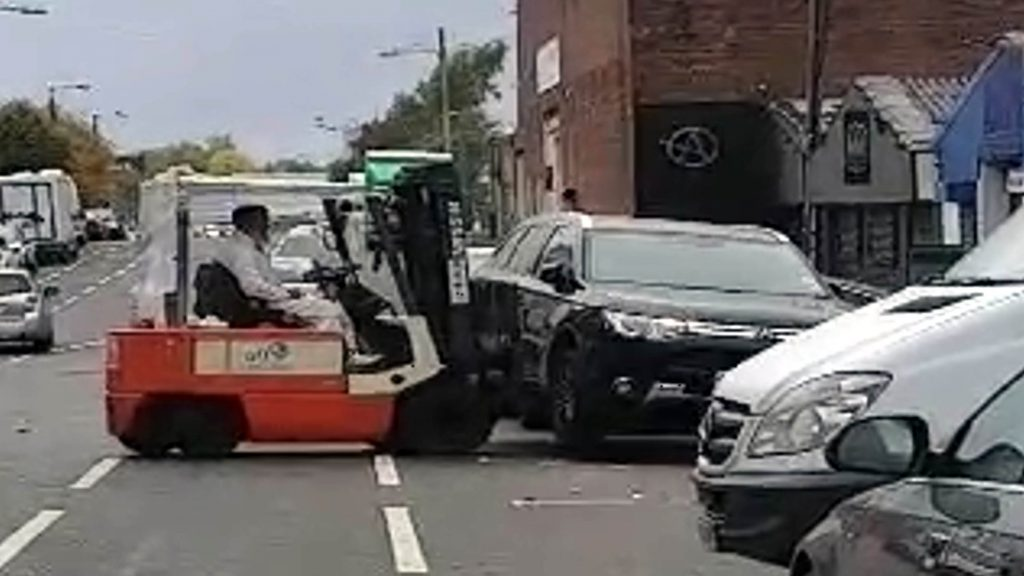 "AMAZING footage shows the moment a ""badly"" parked car was moved in a city street using a fork lift truck."