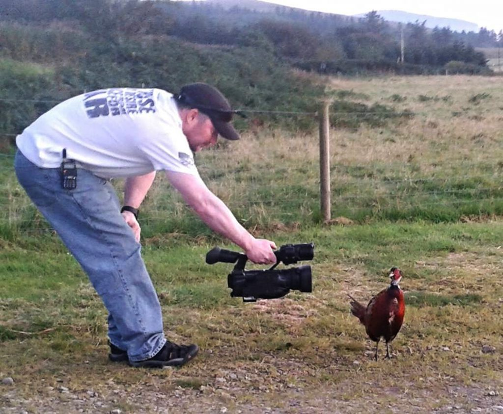 "James films the pheasant before trying to leave in his car AN amazing video shows a frisky pheasant chasing a car - after the bird fell in love with the driver. James Clark found himself the subject of unwanted attention after stopping on an Arran road to photograph and video the game bird. But when James, 44, prepared to leave the grouse started making mating calls and darted back and forth in front of his car. To the businessman's astonishment, the bird then chased his vehicle for several minutes with the hilarious scene caught from the back seat by his son. American James, who was heading home after visiting the island's famous Machrie Stones, said he had often encountered pheasants on Arran but this was the most ""ballsy""."