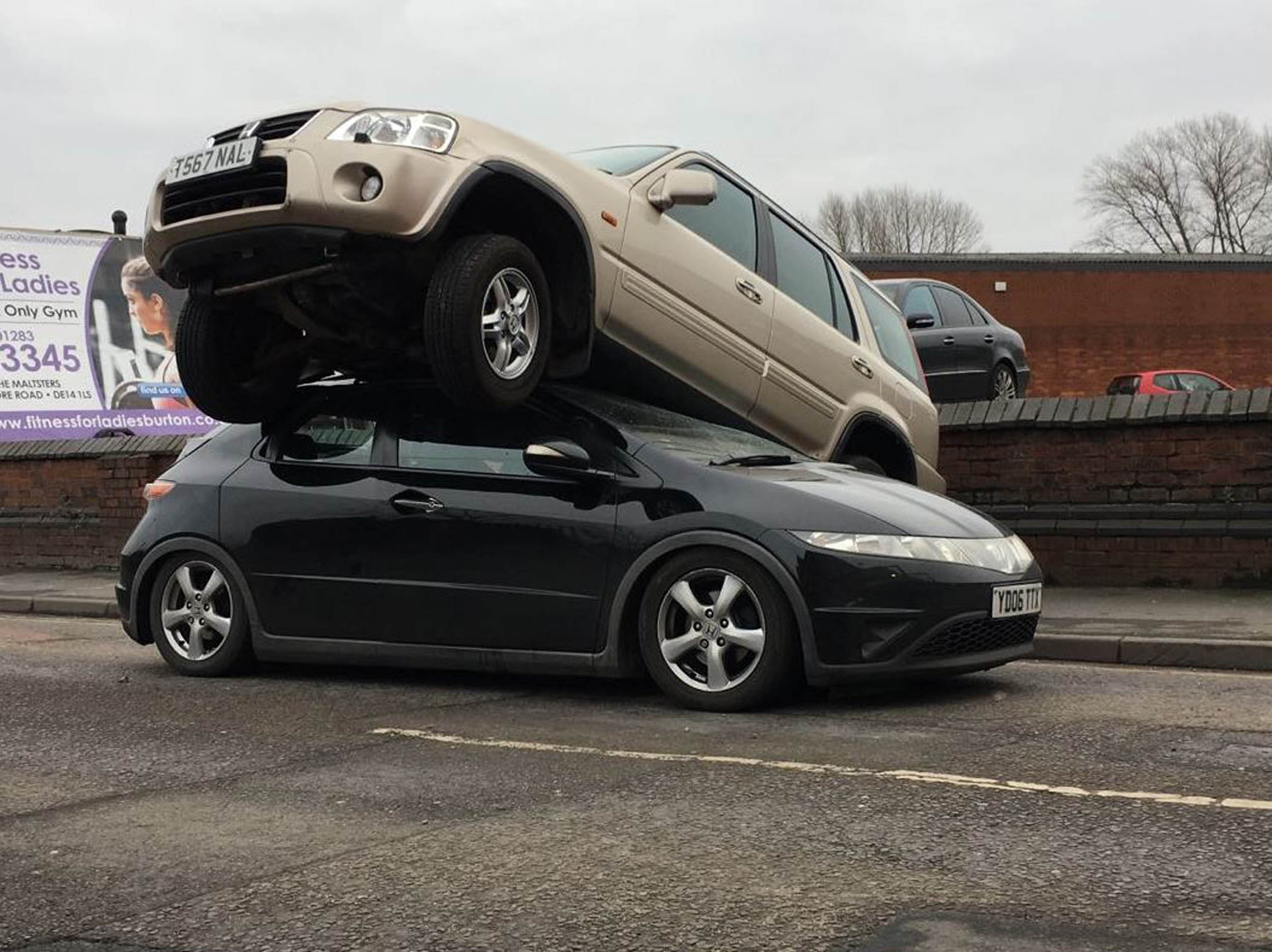 amazing aftermath of suv rocketing from mot test centre and on a spokesman for west midlands ambulance service said the 55 year old w in the bottom car was uninjured and the ambulance service took her home