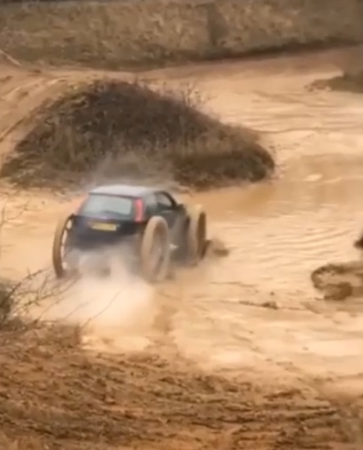 Car blows up sand while driving