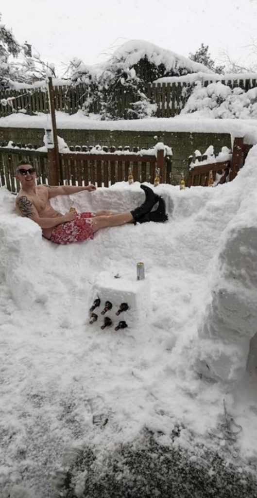 "Stephen Rochester dressed only in swim shorts and reclining on a snow ""sofa"" next to an igloo"
