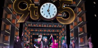 The image shows the cast of the West End production of 9 to 5 The Musical.