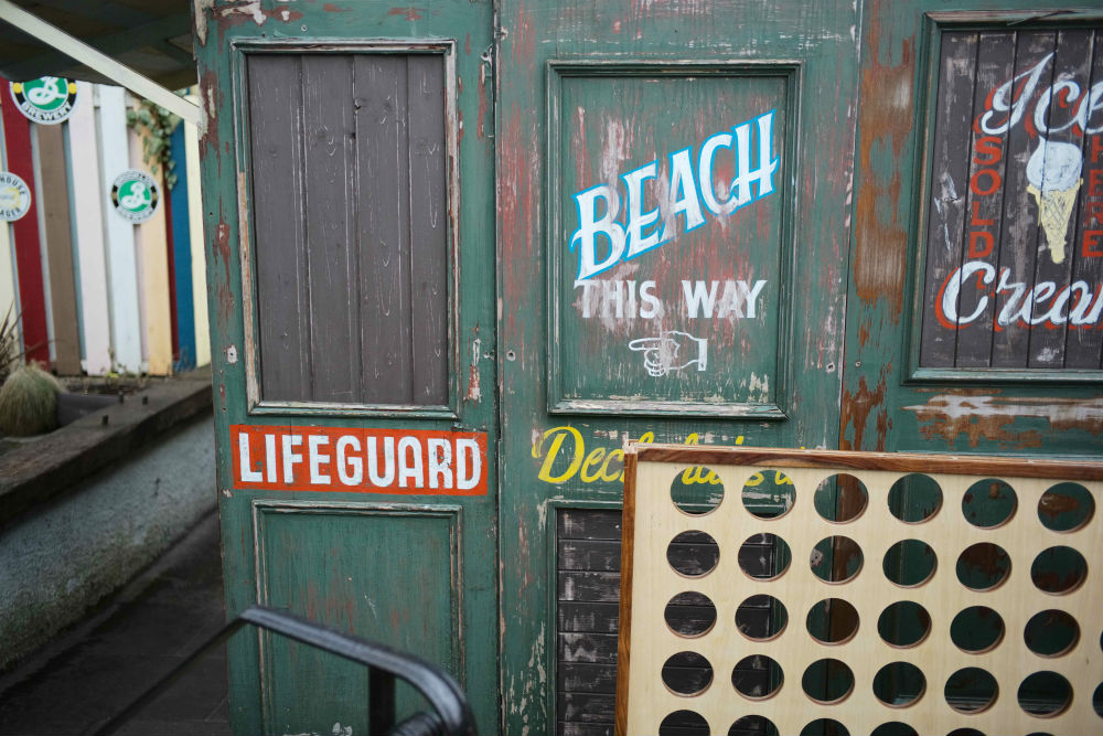 The image shows a lifeguard hut and directions to the beach as part of A Taste of Photojournalism course taken by Luke McAdams.