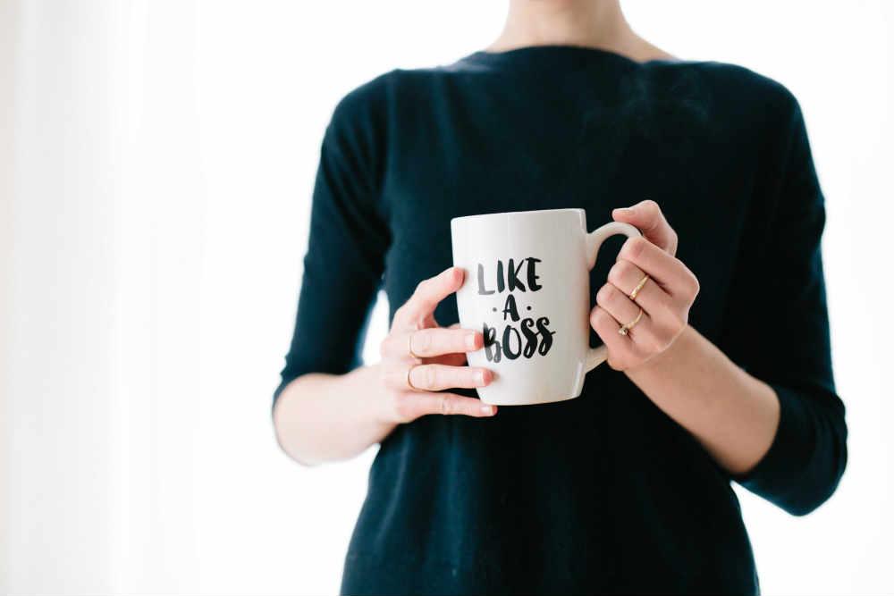 A woman that holds a mug reading 'Like a boss'