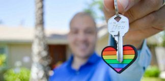Real Estate agent holds up colourful keyring