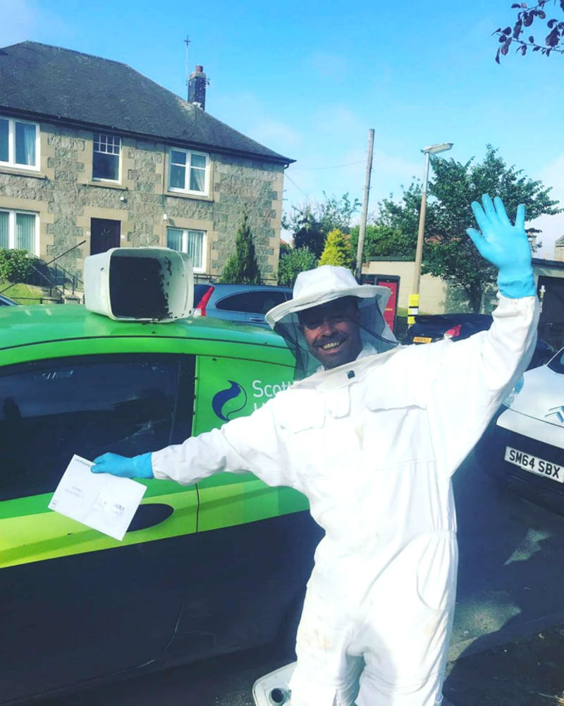 Brian a bee farmer is standing beside the SSE car having got all the bees in a bucket