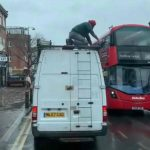 White Ford van with man kneeling down holding onto something