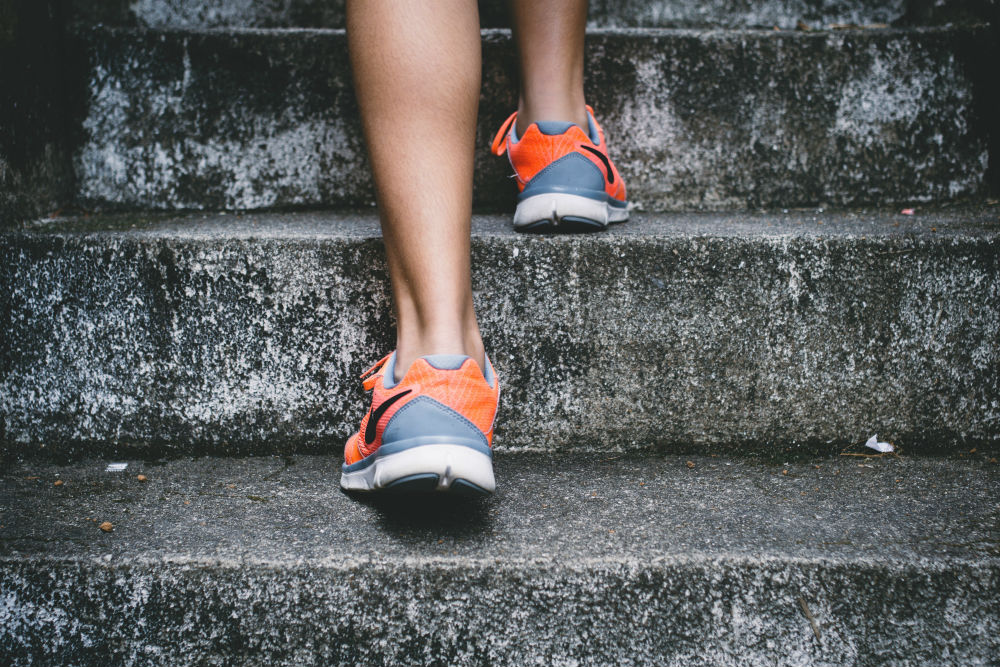 Woman running up steps close-up