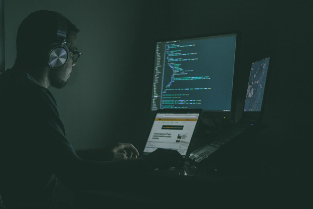A young man coding with headphones in