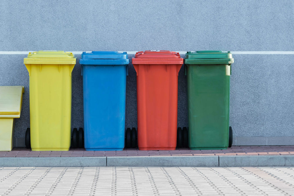 Four bins of different colours l-r yellow, blue, red and green
