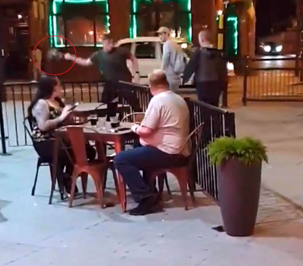 man throws dead pigeon in fight