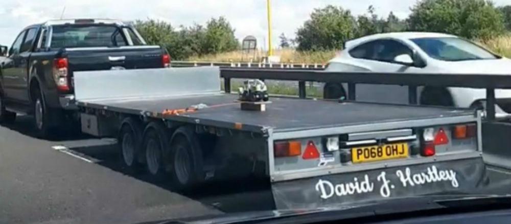 Truck towing combine harvester