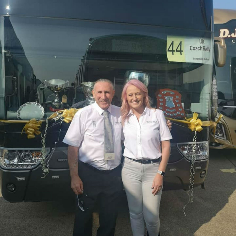 Suzanne and Geoff in front of a coach