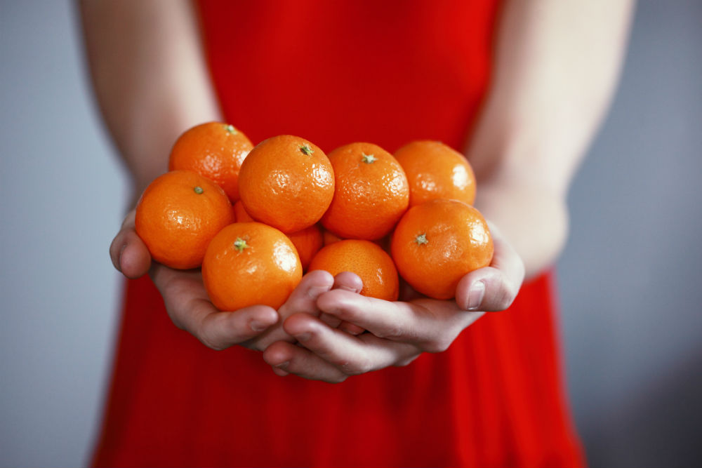 A woman holding oranges