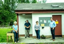 Members of the Shieldaig Community Association gather outside for a photo in front of the public toilets