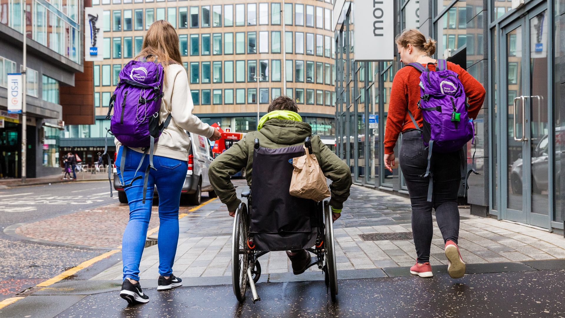 Picture of people walking a man in a wheelchair down a street in Glasgow- Deadline News, Business News Scotland