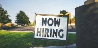 Picture of a sign saying now hiring