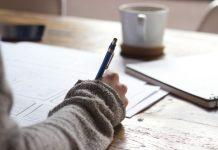 Woman writing essay Photo by Green Chameleon on Unsplash