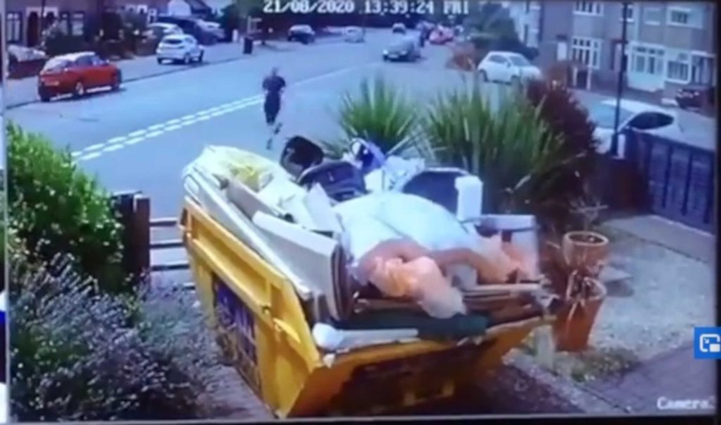 An Amazon driver was caught on CCTV chasing his van as it rolled down a hill before crashing into a wall