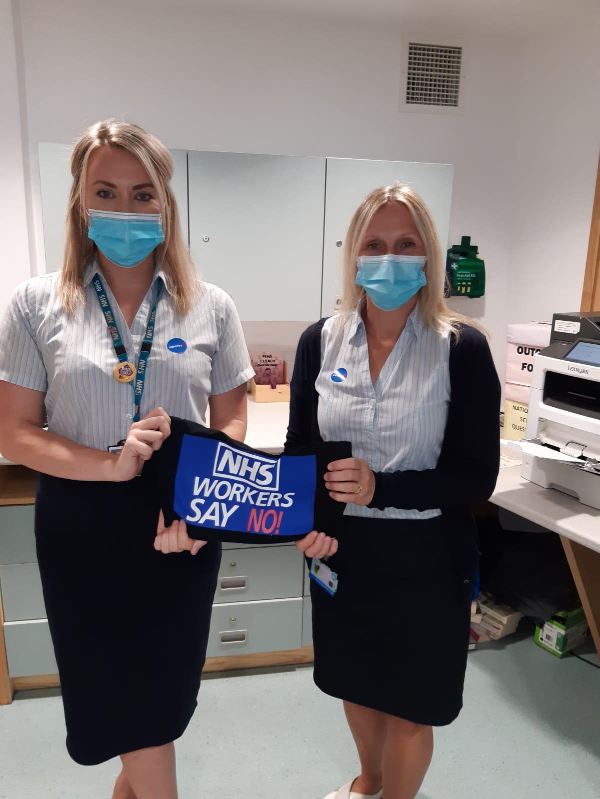 Nurses displaying a banner-Business News