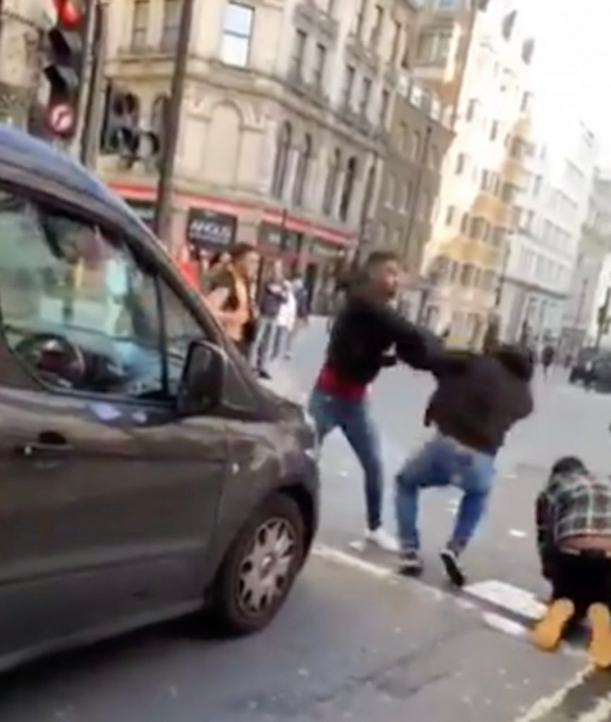 Men fighting on the road near Picadilly Circus
