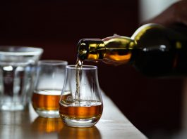 A glass of whisky being poured into a glass