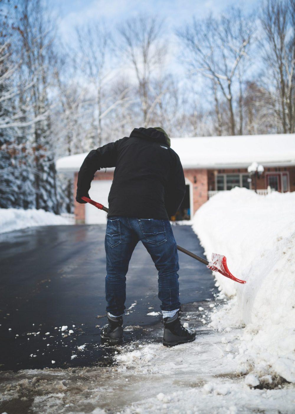 A man shovelling snow on a driveway