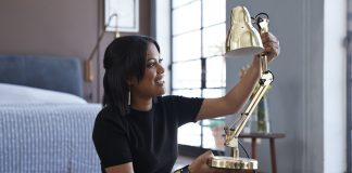 Young woman opening box with lamp at home