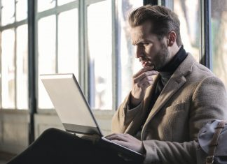 A man thinking looking at a computer - Research News UK