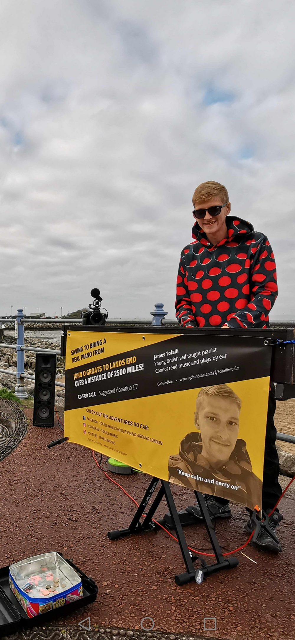 James in a bright raincoat with his poster - Scottish News