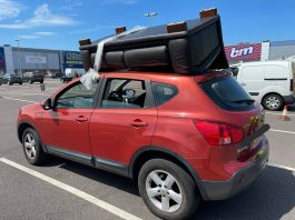 The red Nissan with a sofa tied to the roof   Traffic News UK