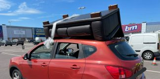 The red Nissan with a sofa tied to the roof | Traffic News UK