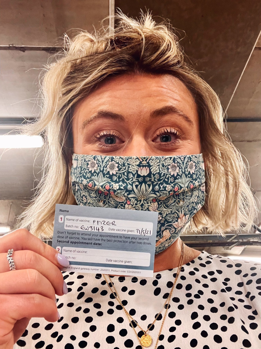Laura Hendry proudly showing off her vaccination card - UK Health News